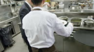 POV waiter taking prepared plates from the plating area in a restaurant kitchen to carry them to the dining room; camera precedes waiter into dining room