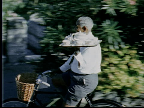 1963 MS PAN Waiter wearing Bermuda shorts rides by on bicycle holding tray with tea service / Bermuda