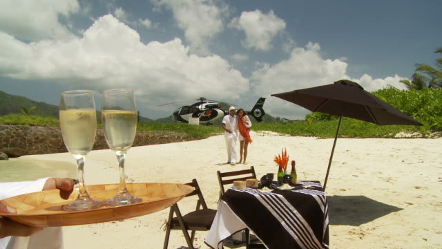 WS Waiter welcoming arriving couple with champagne by table on sandy beach, helicopter on helipad in background / Seychelles