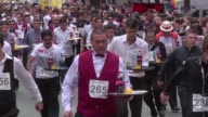 Waiters take part in a century old Argentine tradition of racing down an avenue with tray and drinks without having the bottles fall over