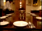 Waiting staff place plates and cutlery on large dining table