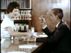 MS Waitress bringing cup of coffee to smoking businessman at diner counter/ USA