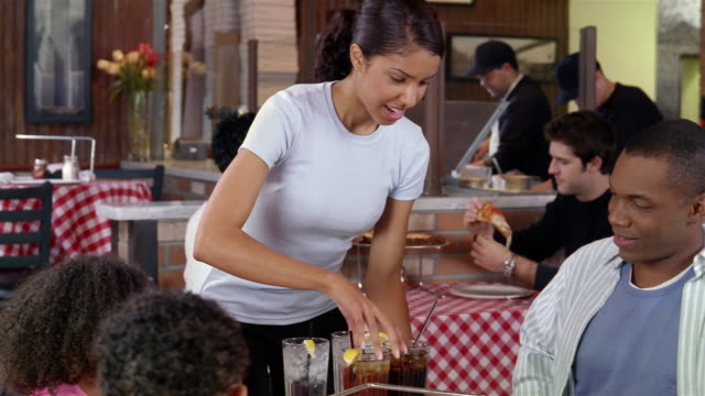 Waitress bringing drinks to family at pizza restaurant / serving drinks