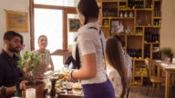 MS waitress bringing menu to group of friends in restaurant