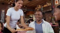 Waitress bringing pie to family at pizza restaurant / putting pizza on stand / family members lifting slices off tray and putting on plates