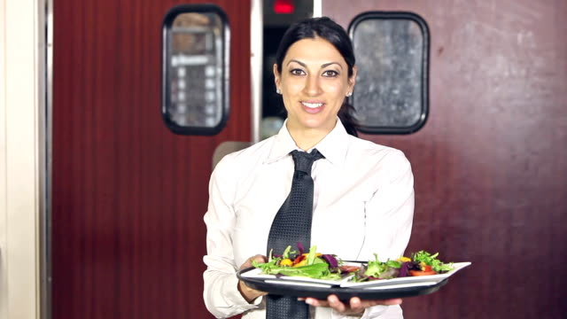 Waitress carrying food out of kitchen in restaurant