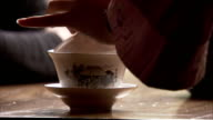 A waitress delicately pours a cup of hot tea for a customer. Available in HD.