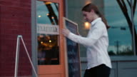 Waitress displays chalkboard sign with dinner specials outside restaurant