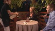 waitress giving menu's to couple at restaurant