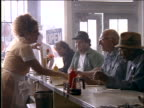 Waitress giving menus to men at counter in diner