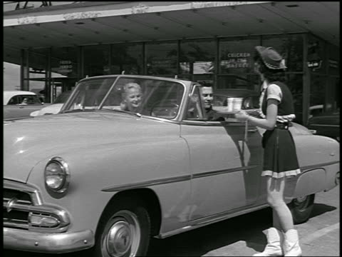 B/W 1952 waitress in cowgirl costume bringing tray to couple in convertible at drive-in restaurant