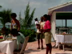 MS,  waitress leading family of four to outdoor table in restaurant,  Harbour Island,  Bahamas