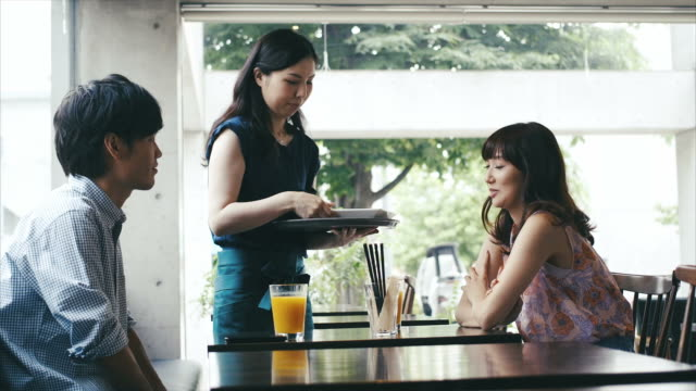 Kellnerin serviert asiatische Paar im Café