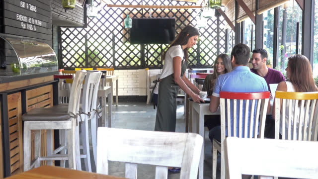 Waitress serving coffee to group of friends