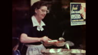 Waitress serving food inside restaurant as viewed through restaurant window / man unloading boxes on the street seen in the reflection of window /...