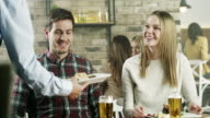 Waitress serving food to young couple