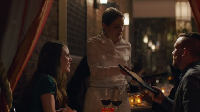 Waitress takes menus from dining couple in upscale restaurant