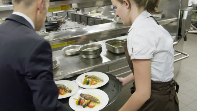 POV waitress taking prepared plates from the plating area in a restaurant kitchen to carry them to the dining room