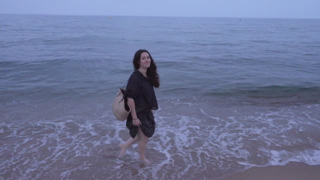 4K | Walk at an empty beach at the end of the summer. Pale woman with long hair dress in dark blue walking barefoot along the shore with feet in the water. She looks to the camera and smiles. She carries a basket in an overcast day at dusk