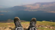 Walker takes rest from Hike - Walking boots overlooking Lake