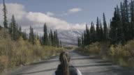 Walking along a rural highway through wilderness