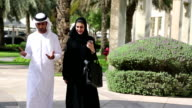 Walking Arab man and woman in traditional clothing