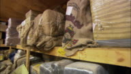MS POV Walking between wooden shelves piled high with bundles of illegal drugs wrapped in plastic and burlap / Nogales, Sonora, Mexico