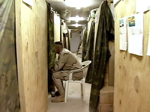 Walking POV down corridor in barracks to room where two men watch TV