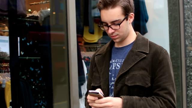 Zu Fuß vorbei an Geschäften mit einem smartphone.