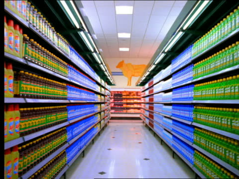 Walking point of view supermarket aisle stocked with colorful cleaning supplies