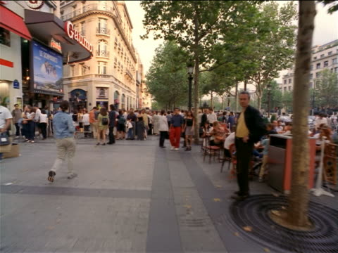 Walking point of view through crowd on sidewalk of Champs-Elysees, past trees + stores / Paris, France