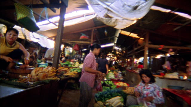 Walking point of view through food market with shoppers and vendors / Cambodia