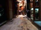 Walking point of view through marketplace alleyway past man sweeping / Khan al-Khalili / Cairo, Egypt
