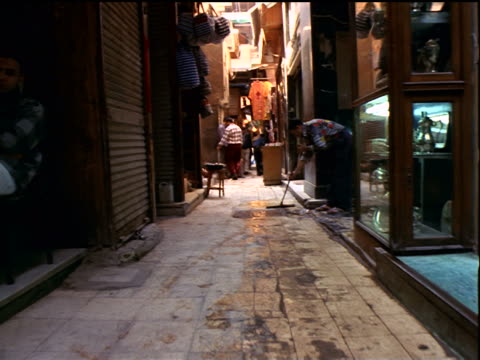 Walking point of view through marketplace alleyway past man sweeping / Khan al-Khalili / Cairo, Egypt