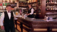 Walking point of view toward waiter putting coffee cups on counter / waiter with tray passes in foreground / Florence