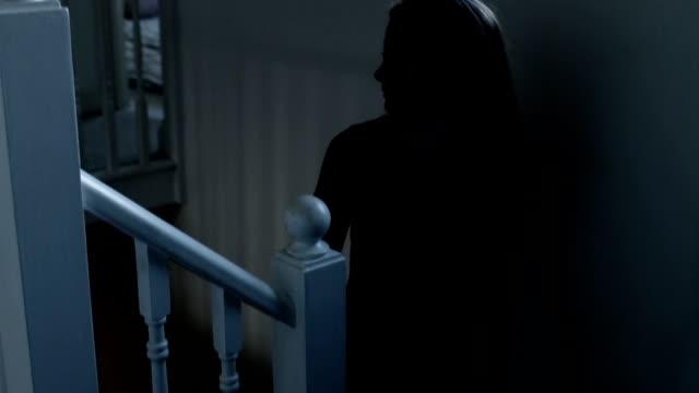 Walking upstairs, entering a dark room.