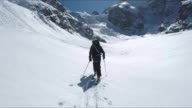 Walking with ski on the fresh snow in Glacier sorround by mountains