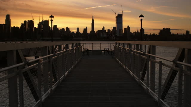 A walkway bridge looks out over the Hudson River to Midtown Manhattan.