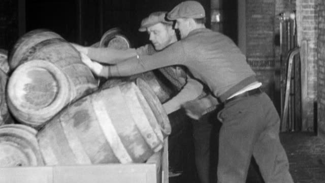 wall of beer barrels / men loading barrels onto back of delivery truck / man with watch signals midnight and the trucks drive off to deliver alcohol...