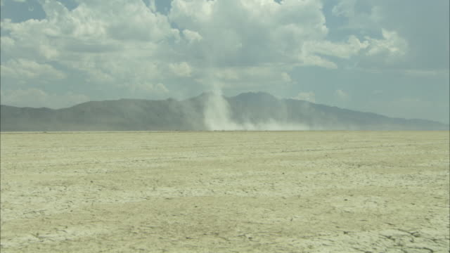 Wall of dust blowing frm cracked desert floor
