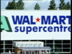 Bristol EXT/ITN WS cars into parking area of ASDA Walmart store/ GVs Wal Mart supercentre/ shoppers loading car with shopping GVs shoppers inside...