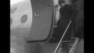 Walter C Robertson US charge d'affaires in Chongqing down steps of American transport C54 plane as he arrives in Peiping / Chinese Communist Army...