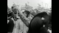War ship USS Enterprise entering San Francisco harbor after eight months in Vietnam / women on shore wave to sailors on ship / sailors walk down...