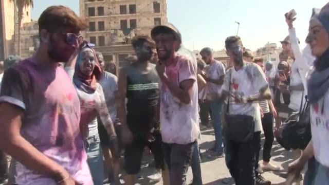 War weary residents of Syria's Aleppo took to the streets in a rare street festival to dance hurl brightly colored dyes and unveil a new public art...