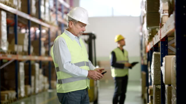 Warehouse Employee Scans Codes With Smartphone