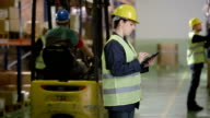 Warehouse Employee Using A Digital Tablet