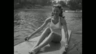 VS Warner Brothers actresses Phyllis Coates and Patricia Northrup in halter top bathing suits each ride a Motorboard motorized surfboard around small...