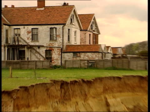 Warning of rising sea levels ITN Norfolk Happisburgh Houses PULL OUT to show how close they are to the cliff