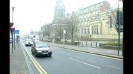 EXT Exterior of Leeds Town Hall and traffic passing Local bus towards and past along high street