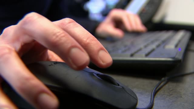 Warning over rise in 'sextortion' online blackmail ENGLAND London Reporter sitting at computer Close shot hands using mouse ITN Reporter listening to...